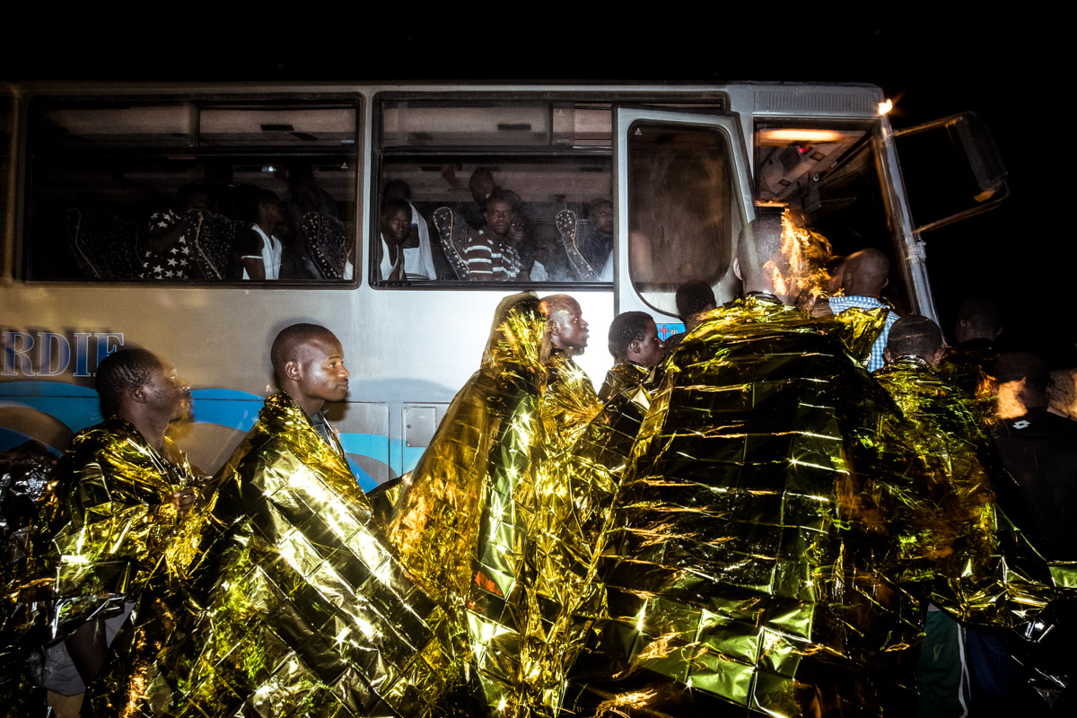 28/08/2016, Lampedusa (Italy). In the island's harbour, some of the 240 migrants rescued at sea by the Italian Coast Guard board a bus that will take them to the island' reception centre for migrants.