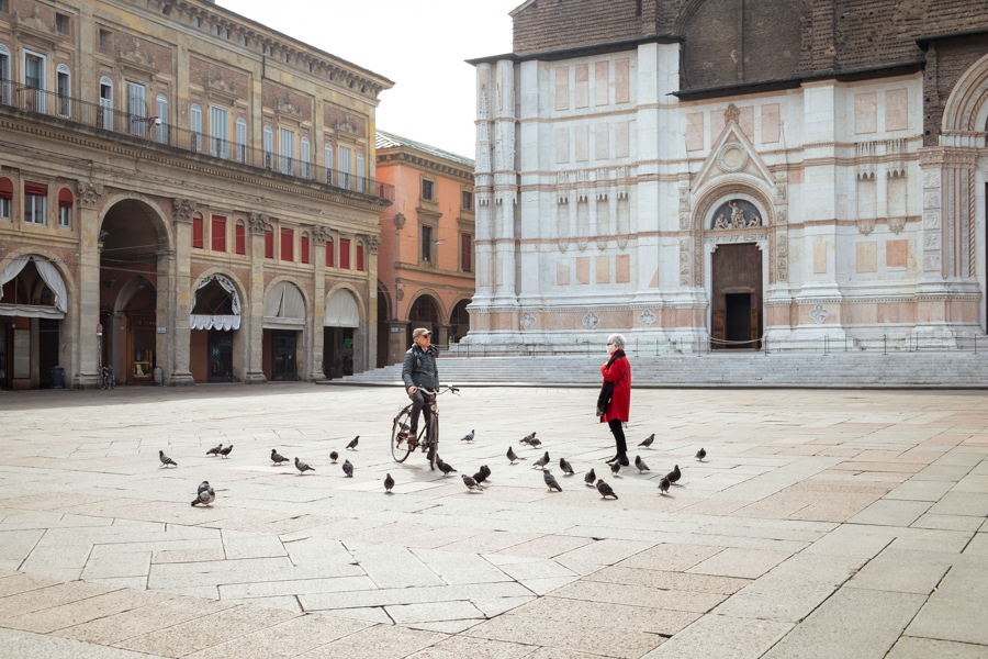 Bologna (Italy), March 13th 2020. In an unusually empty Piazza Maggiore (the city's main square) an encounter between a man and a woman is held keeping a safety distance. Only pigeons surrounds them and the woman wears a medical mask. Following the outbreak of Covid-19 in Italy, a nationwide lockdown was declared on Mar 9th 2020 and gradually lifted between May 4th and Jun 15th.