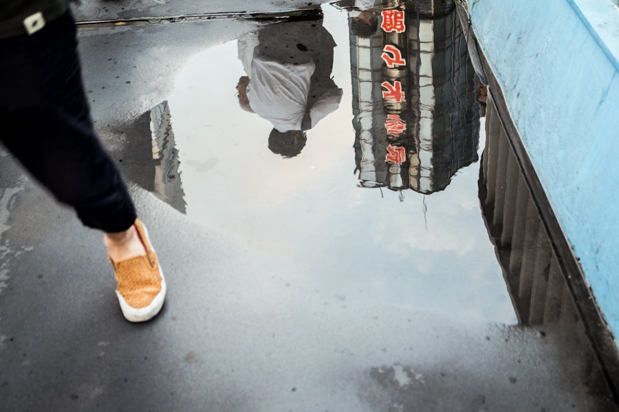 """A woman and a man, reflected in a puddle, walk in opposite directions in a street of Tokyo. Japan is globally considered the """"black hole"""" of child abduction in case of separation: every year nearly 150,000 parents are cut off from their children's life by their partners."""