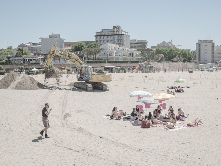 Cattolica, Italy, 27 May 2020. A group of young sunbathers at the beach and a bulldozer working in the background. The tourist season take-off period in the Italian 'Riviera Romagnola', in late May, coincides in 2020 with the end of a 3-months lockdown for Covid-19 in Italy. Half-empty beaches, face masks, and delayed urbanization works are the image of an atypical season start.