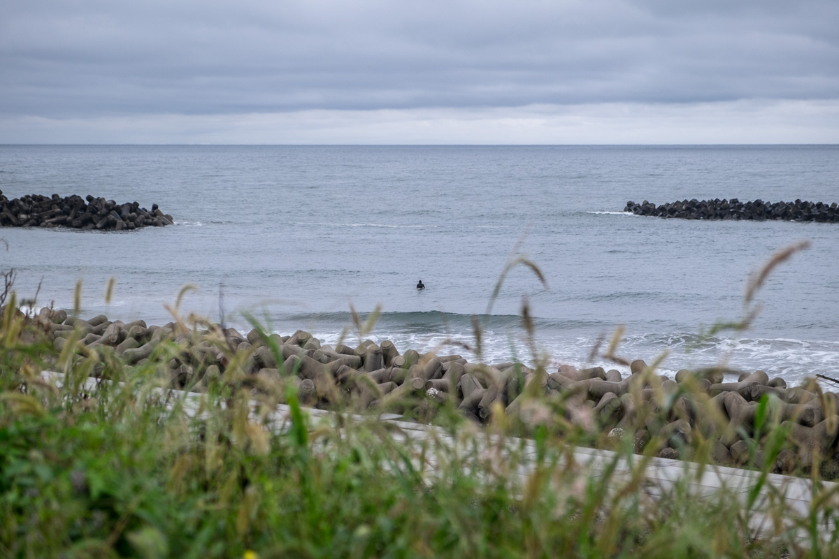 Near Watari (Japan), September 10th 2018. Even though an ordinance dating back to the immediate earthquake aftermath still forbids bathing in the ocean along the coast of Tohoku, a man swims close the newly build seawall near the town of Watari.