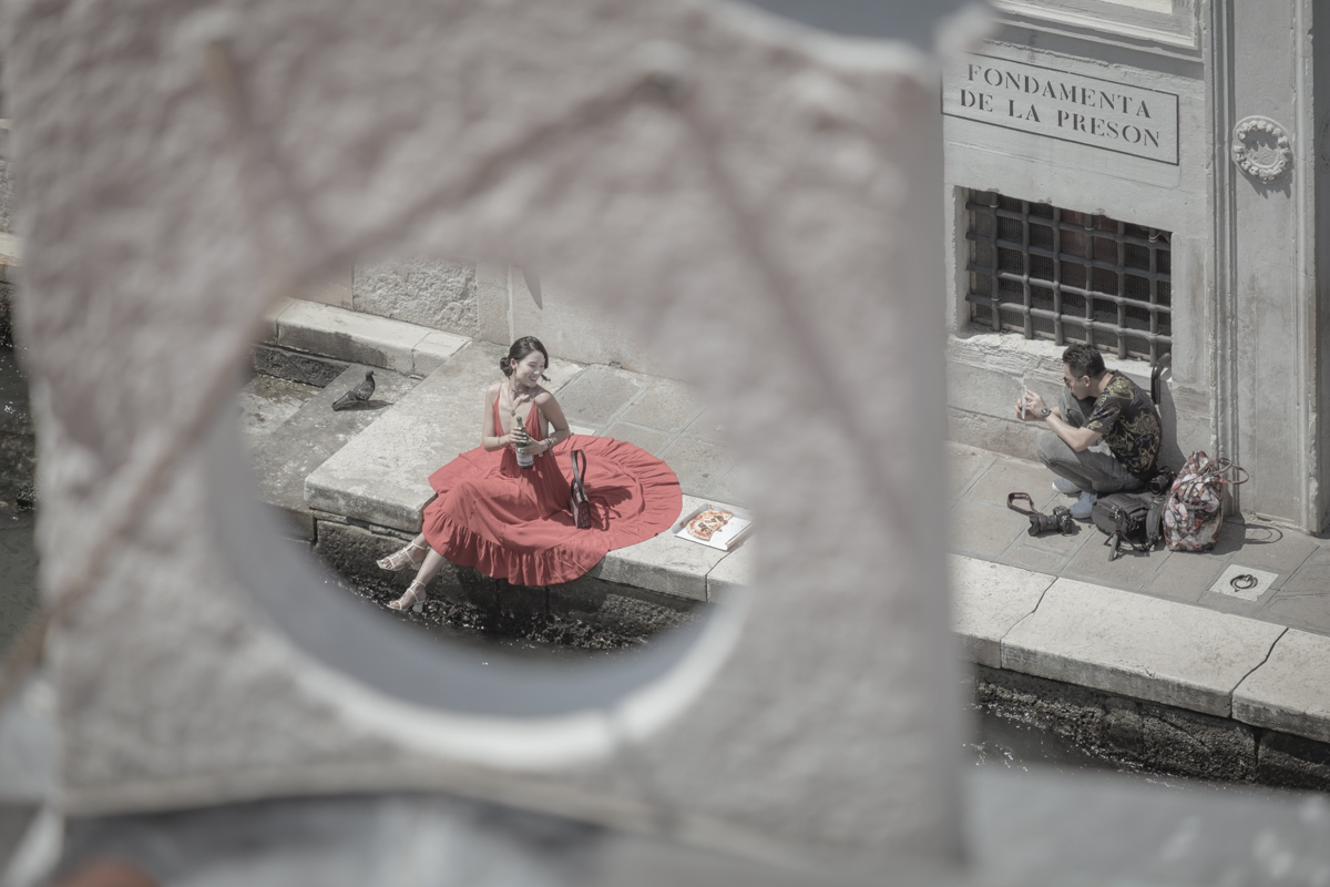 An Asian model poses for a photo shoot along Venice's Grand Canal, near the Rialto Bridge. The photo set re-enacts a stereotypical 'Italian scene', including a waterside pizza picnic, an Italian water bottle and a designer handbag.