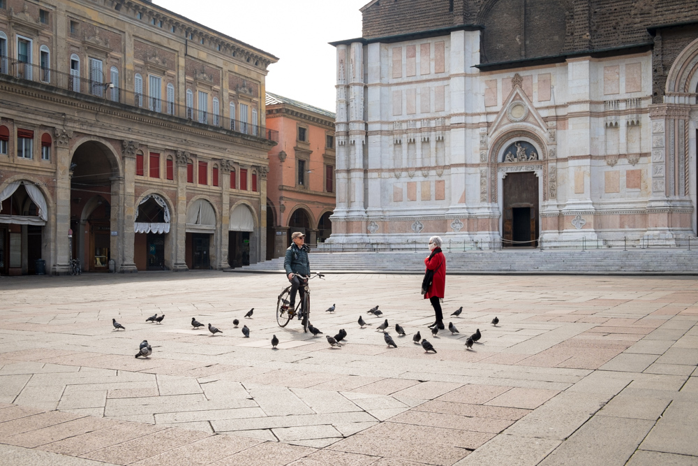 March 13th 2020, Bologna (Italy). In an unusually empty Piazza Maggiore (the city's main square) an encounter between a man and a woman is held keeping the safety distance imposed by the Italian authorities as a measure to fight the Coronavirus (Covid-19) outbreak. Only pigeons surrounds them and the woman wears a mask. In March 2020, following the outbreak of Coronavirus (Covid-19) started in Italy in late February 2020, the Italian authorities imposed very drastic measures to try and contain the contagion. Amid fear for a collapse of the public health service, since March 9th the entire country is in lockdown: people are allowed to leave their houses only for primary needs, and social distancing (keeping a safety distance from each other) is imposed by law. These measures are enforced by the police, and those not complying with them may face harsh sanctions and even jail.