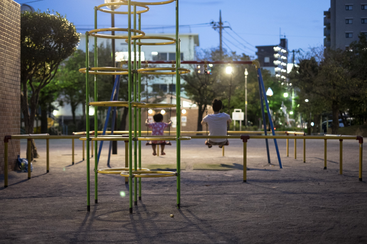 At dusk, a father and his child play on a swing in a children's playground in Tokyo.