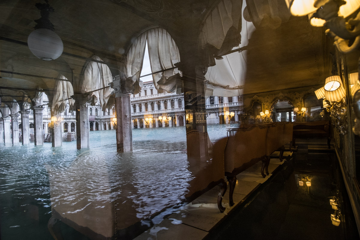 Nov 15th 2019. A flooded St. Mark's Square reflected in the window of an historic cafè, also flooded with water.